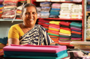 Woman sitting in fabric shop in India.